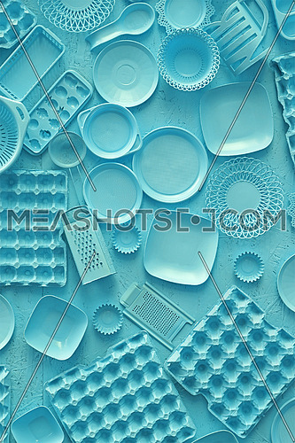 Close up flat lay of different blue color painted kitchen utensils and tools, grater, spoon, egg carton, plastic disposable plates, elevated top view, directly above