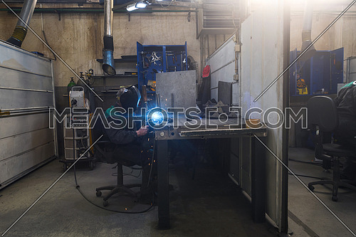 Professional welder performs work with metal parts in factories, sparks, and electricity. Industry worker banner. High quality photo