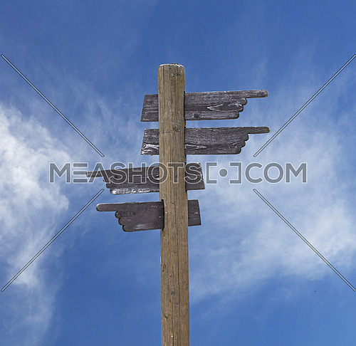 Old vintage road signpost with four hand shaped wooden planks blank copy space arrows different directions, left down and right, over blue sky background, low angle side view