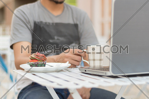 man siting behind a laptop computer holding a mug