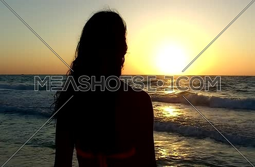 beautiful Woman going into sea during sunset