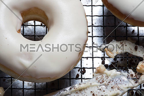 top view of white glazed donuts and walnuts and white chocolate paste on a net
