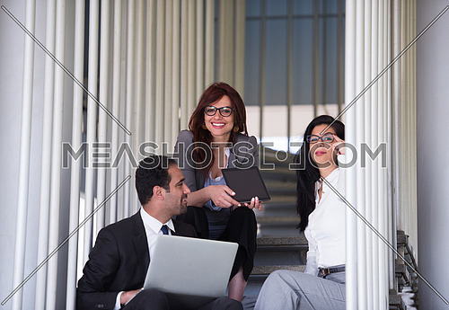 Young executives sitting on the steps of a corporate office building discussing business using laptop and tablet