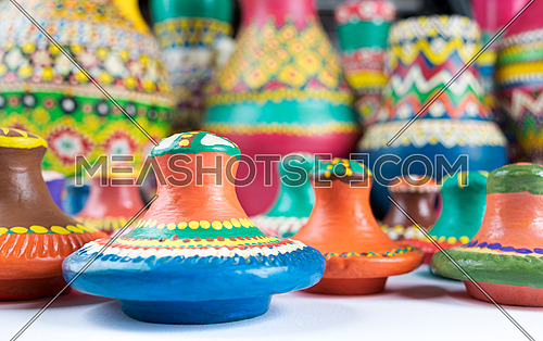 Still life of colorful pottery lids on blurred background of colored pottery vases