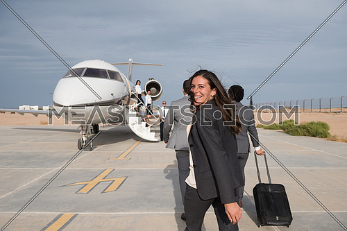 young successful middle eastern business woman walking with their business partners in front of private airplane