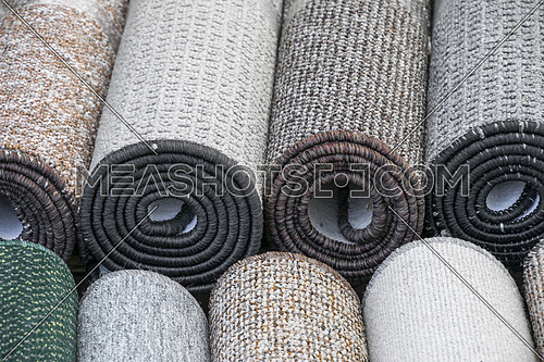 Close up rolls of flooring fitted carpet mats on retail display, high angle view