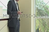 Medium shot for a male business man wearing suit and using his smartphone at day.