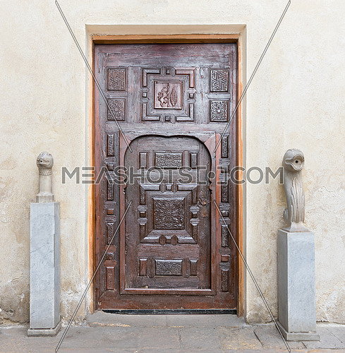 Wooden aged engraved decorated door and stone wall, Medieval Cairo, Egypt
