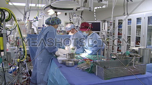 Tilt Down long shot of operating room while medical team performing surgery