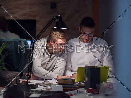 young designers working on a new project in the night startup office using modern technology
