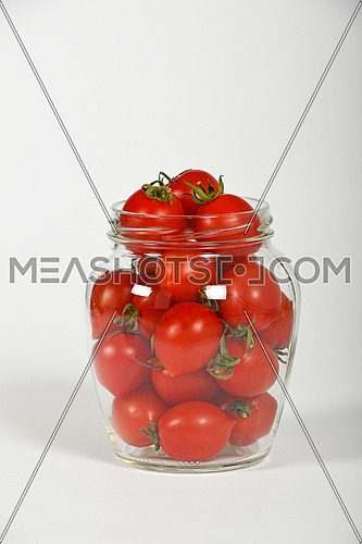 Glass jar full of red cherry tomatoes ready to pickle for conservation over white background, side view