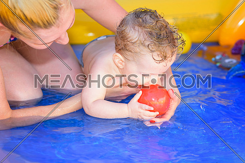 Mother and son play in a small paddling pool
