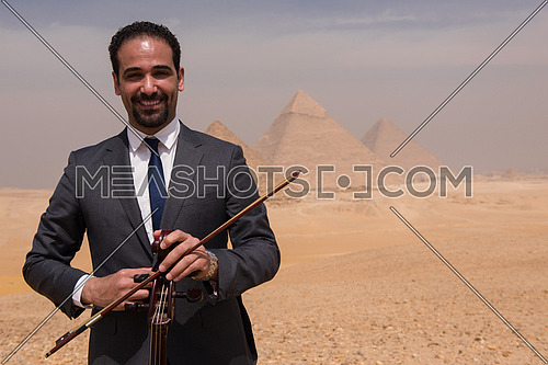 chello player in egyptian desert with pyramids in background