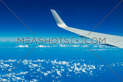 Looking through aircraft window during flight. Aircraft wing over blue skies and white clouds.Copy space.