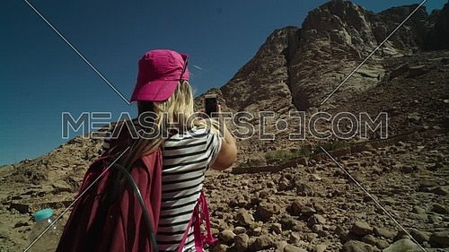 Follow shot for a female tourist wearing a pink cap and travel backpack taking a selfie at Sinai Mountain for wadi Freij at day.