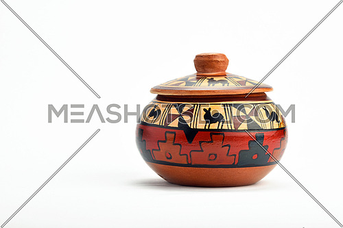 Painted handmade traditional Latin American ceramic pot with closed lid isolated on white background