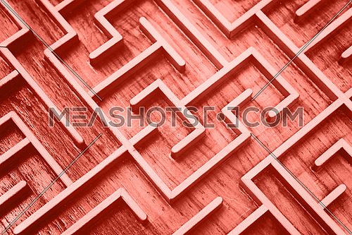 Close up coral pink color toned wooden labyrinth maze, toy puzzle game, elevated high angle view