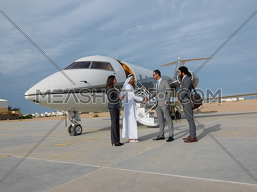 Young successful businessmen shake hands with their Arab business partner in front of the private airplane