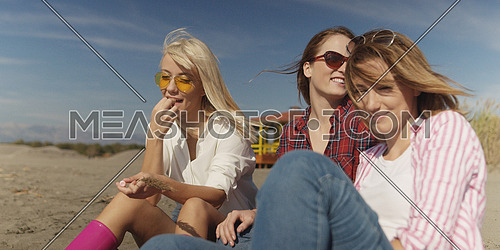Group Of Young girlfriends Spending The Day On A Beach during autumn day