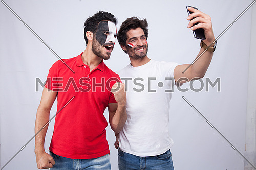 two young men standing on a white background taking a selfie