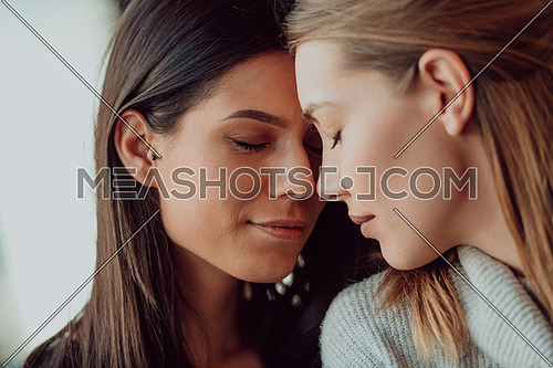 two lgbt girls romantically embracing sitting in a modern cafe