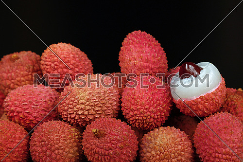 Heap of fresh picked red ripe litchee (Litchi chinensis) tropical fruits with one lichee open and peeled, isolated on black background, close up, low angle side view