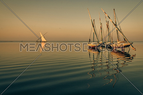 sail boats parked in the middle of a lake