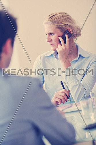 blonde young business woman talk by cellphone on meetng