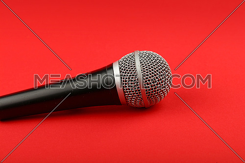 Black and silver vocal microphone side view close up on red background
