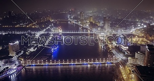 360 Drone shot over Cairo until reach The River Nile showing Bridges and Novotel Hotel and then fly over the River Nile at night