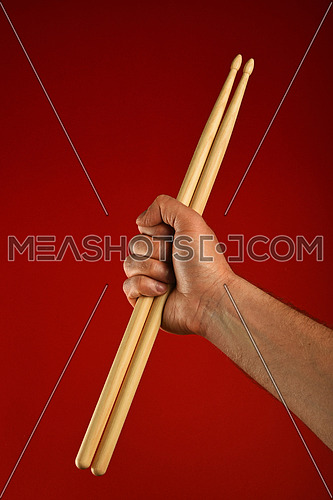 Man hand holding two wooden drumsticks over red background, diagonal, close up