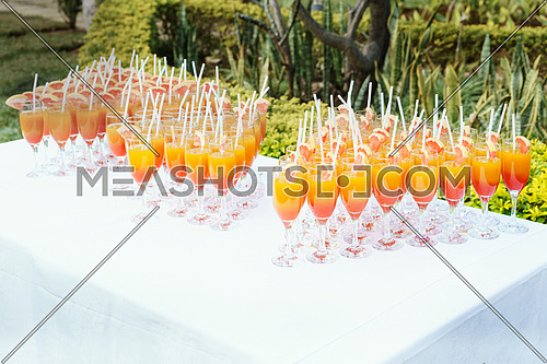Orange juice cocktail in a flute glasses and slice of fresh orange with draw on white table,Party outdoor.