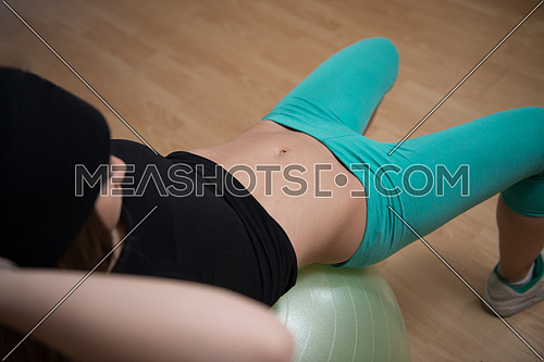 Young Woman Exercising Abs On Ball Workout Posture In Fitness Club