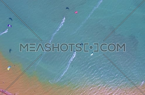 Drone shot flying above the red sea while Kite surfers are surfing  at Day