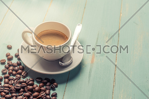 White cup of coffee,teaspoon and coffee bean on green background. Copy space.