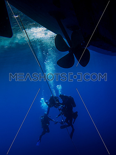 Divers performing their Safety stop under the boat under water