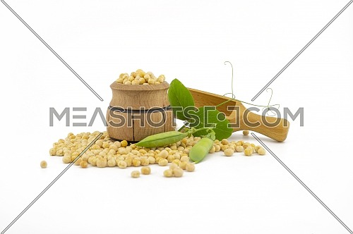 Dried peas spilling from a wooden barrel, wooden scoop and fresh plant with pods isolated on a white background