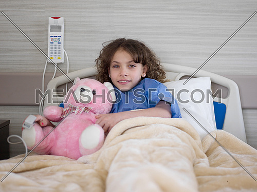 young girl lies in a hospital bed while hugs beauty pink teddy bear