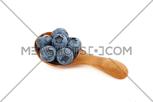 Close up several fresh blueberry berries in rustic natural wooden scoop spoon isolated on white background, high angle view