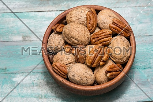 Pecan and walnut on wooden background. Healthy food