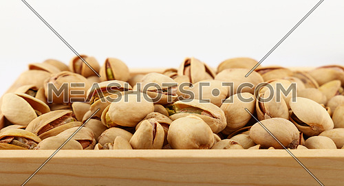 Close up fresh roasted pistachio nuts in wooden box over white background, low angle view