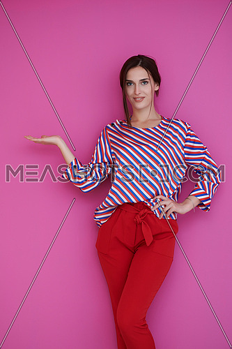 Portrait of happy smiling young beautiful woman in a presenting gesture with open palm isolated on pink background. Female model in modern fashionable clothes posing in the studio