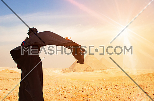 egyptian woman in bedouin traditional clothes in front of ancient giza pyramids