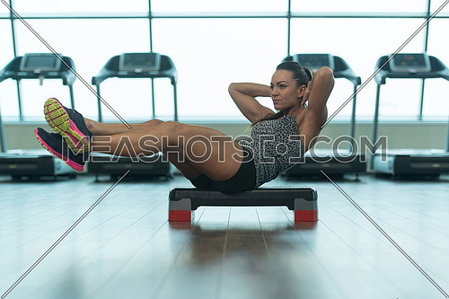 Young Woman Athlete Doing Abs Exercise On Stepper As Part Of Bodybuilding Training