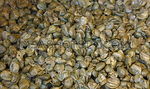 Green pickled small capers (flower buds) close up background, retail market display, high angle view