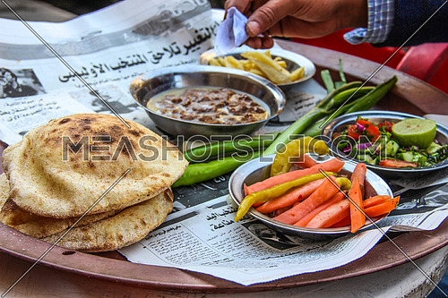 a photo for a traditional breakfast served in a street coffee shop in Cairo, Egypt showing the bread , pickles and beans