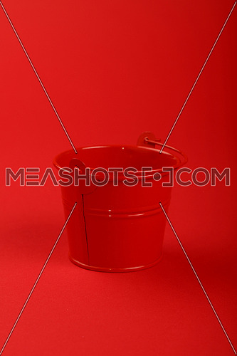 One small red painted metal empty toy bucket over red paper background, close up, high angle view