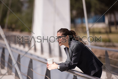 young business woman drinking fresh  morning coffee while walking across modern bridge to shes job