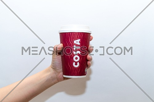 A female holding Costa Coffee red cup on a white background, December 2018 in Cairo- Egypt