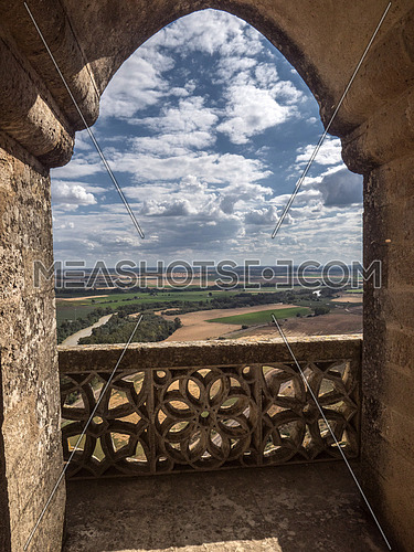 Almodovar del Rio, Cordoba, Spain - June 9, 2018: Ogival Arch of balcony in a tower, landscape of Cordoba countryside, It is a fortitude of Moslem origin, it was a Roman fort and the current building has definitely origin Berber, placed close to the Guadalquivir, take in Almodovar of the Rio, Spain